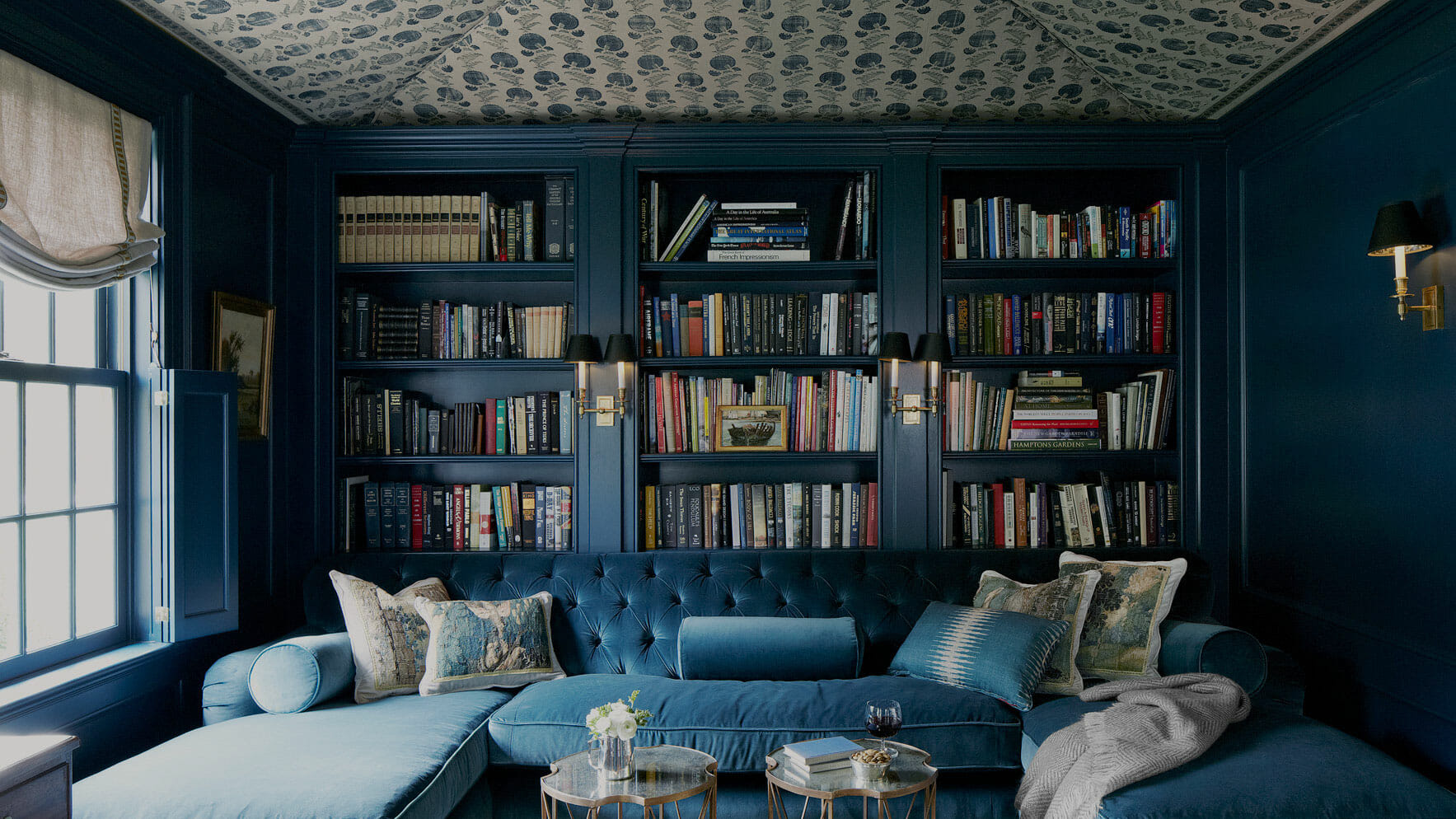A home study room with blue walls and built-in bookshelves full of books.